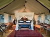 Duba Plains Camp, canvas tent interior with four poster bed, mosquito netting and lovely wooden furnishings