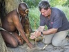 Khalahari Plains Camp, native dressed in traditional  oufit teaching guest how to light a fire by twisting stick to create friciton, fire starting