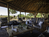 Kwetsani Camp, grooved pole canoe, guide staffmember poling guests along river, swampland, Botswana, Africa, pride