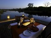 Savuti, exclusive private dining table overlooking your own personal section of paradise, lit by warming lanterns and protected by railing in Botswana