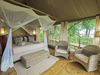 Jacana Camp, spacious bedroom with accompanying reading chairs, camopied bed area, wonderful views of Botswana wilderness and Okavango Delta, green