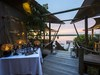 Duma Tau Camp, central area with wine selections and view of hippo lagoon at sunset, extending pathway to firepit and edge of lagoon, African safari
