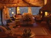 Borana Lodge, sprawling indoor lounge area with stucco fireplace for warmth and windows at every turn for perfect wildlife emersion, Kenya, Africa