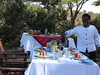 Borana Lodge, safari staff member smiles as he prepares a tasty breakfast for safari guests out by some sheltering trees in the bush, Kenya, Africa