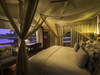 Seba camp, large king bed in expansive master bedroom suite with decorating photos of natives in Botswana, Africa safari