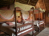 Lewa Wilderness Lodge, two queen beds with tasteful canopies encircling give off an inviting appeal to the large bedroom, African safaris, Kenya