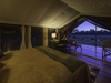 Little Governor's Camp, view of the African savanna from the inside of the large master bedroom suite through the open tent flap, Kenya, Africa safari