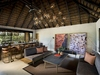 modern bar and lounge with thatched roof and gray tweed sofas bird plumage photography artwork lion sand ivory lodge