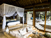 Vumbura Plains Camp, prettily decorated master bedroom with wonderful wood flooring and a twisting canopy for bug protection in Botswana, Africa