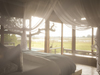 Vumbura Plains Camp, gorgeous master bedroom with king bed and overhanging canopy with inset couch for wildlife viewing through surrounding windows