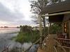 Jacana Camp, edge of deck with panoramic views of Okavango Delta at sunset, enclosing railing, wooden deck, luxury accomodations, Africa, Botswana