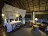 Savuti, expansive master bedroom suite with beautiful white canopy and spacious lounge area for relaxing in Botswana, Africa safaris