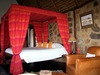 Borana Lodge, master bedroom with stone inlaid walls and vibrant bright pinkish orange canopy surrounding large king bed in Kenya, Africa safaris