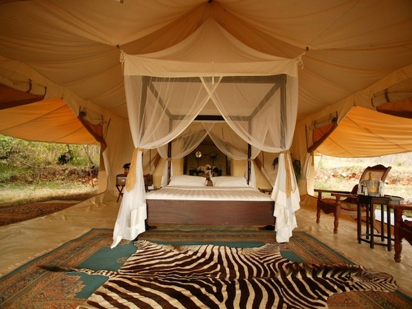 cottars camp luxurious master bedroom with large king bed and white expansive canopy with wood