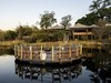 Duma Tau Camp, raised circular fire deck area with surrounding chairs, floating over water, Okavango Delta, hippo filled lagoon, Botswana, Africa
