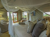 Jacana Camp, luxurious bedroom with large bed, overhanging canopy for insect protection, canvas walled room, sliding glass door, squishy pillows,