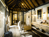 Kings Pool Camp, indoor seating area with intimate small tables, wall display, Africa, Botswana safari, open to the air, wooden chairs