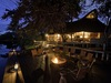 Savuti, beautiful outdoor dining area lit by a multitude of candles and intimate lanterns overlooking the quiet watering hole in Botswana, Africa