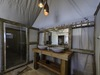Tobu Tree Camp, dual vanity sinks with large shared mirror, enclosed large shower and tasteful lighting in bathroom of luxury Africa safari, Botswana