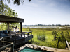 Vumbura Plains Camp, relaxing outdoor lounge space with expansive views of the lush green African savanna in Botswana, Africa safaris