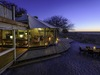 Khalahari Plains Camp, indoor/outdoor lounge area, dining table on sandy area, extensive surrounding wood deck for great views, dusk in Africa