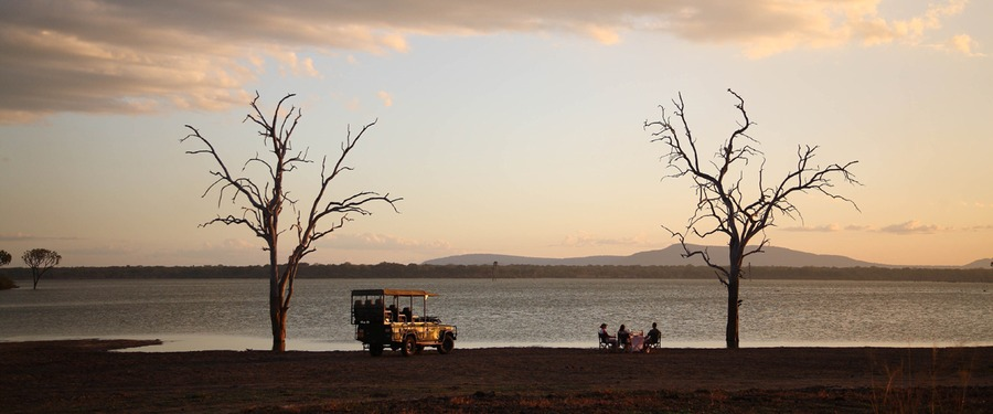 Safari guests eat a luxury picnic by Lake Malawi in southern Tanzania at sunset, a couple of crooked dead trees, safari vehichle, African safari