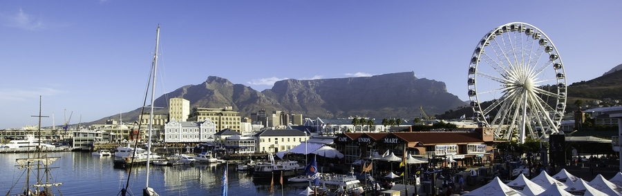 Victoria & Alfred Waterfront, Cape Town, South Africa, view of waterfront town with sweeping mountains in the background, ferris wheel, old sailboats