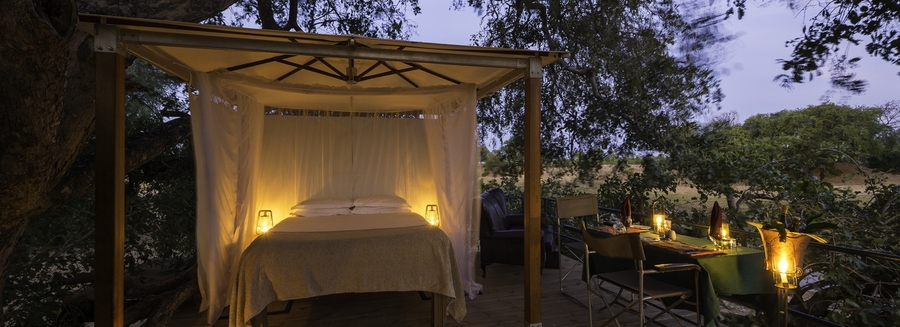 New luxurious sleepout at Ruckomechi safari camp, beautifully lantern lit outdoor bed safely enclosed within the camp, secluded private dining table