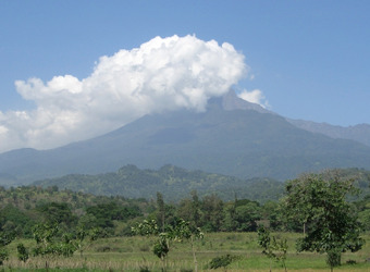 A cloud covers the top of Mount Meru, and the jungle area surrounding the peak is lush and green from rain in Arusha, Tanzania