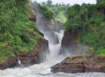 Murchison Falls thunder through the rocky valley creating vicious white water complimented by bright green grasses