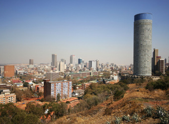View of the city of Johannesburg from several miles away showing the skyline and a large grainery in South Africa