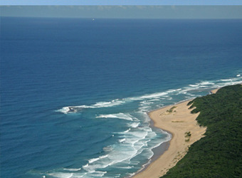 Overhead shot of Rocktail Bay as the ocean lightly caresses the light sandy beaches contrasting against the deep blue ocean, Zuzuland, South Africa