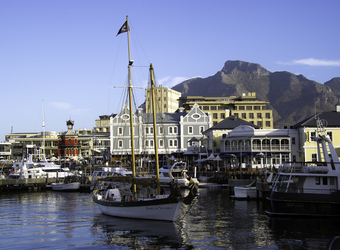 Cape Town, where the Indian and Atlantic Oceans meet, view of the ocean and sailboats and quaint beautiful houses with a huge mountain in South Africa
